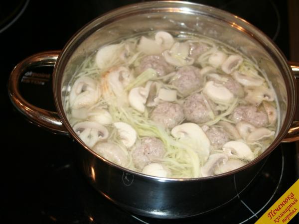 11) Отправляем нарезанные грибы в суп. Все вместе провариваем до готовности еще минут десять. Затем заправляем суп тушеными овощами. Добавляем лавровый лист, черный молотый перец и зелень по вкусу. Доводим овощной суп с мясными фрикадельками до готовности на медленном огне.