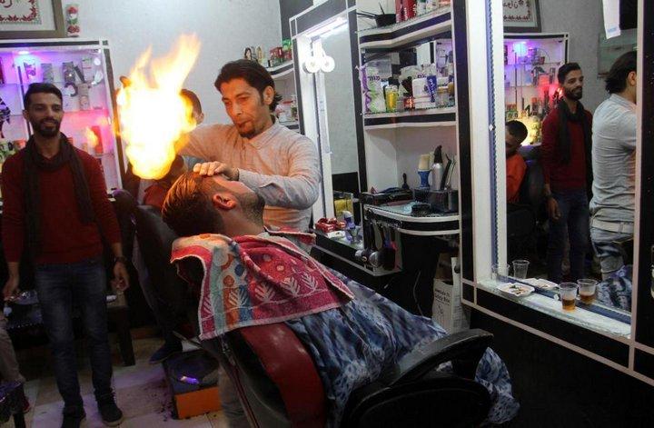 Палестинский парикмахер делает укладку огнём