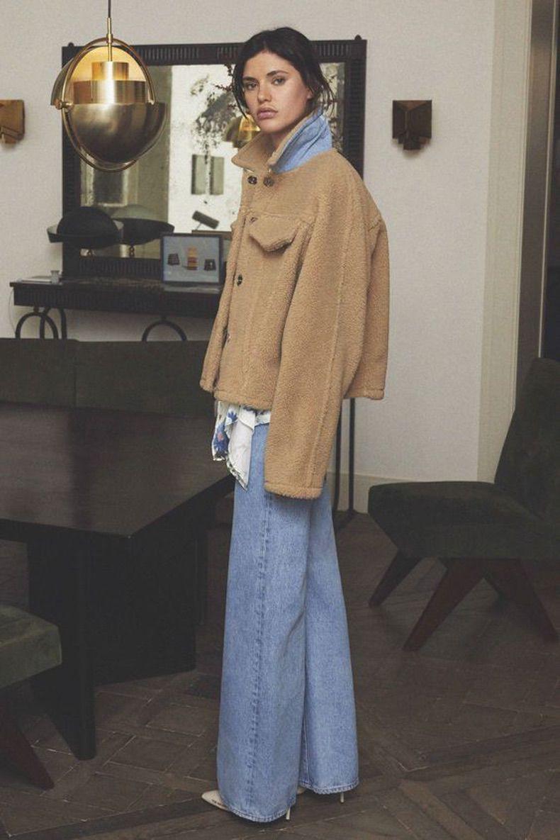Девушка в джинсах клеш и меховой куртке