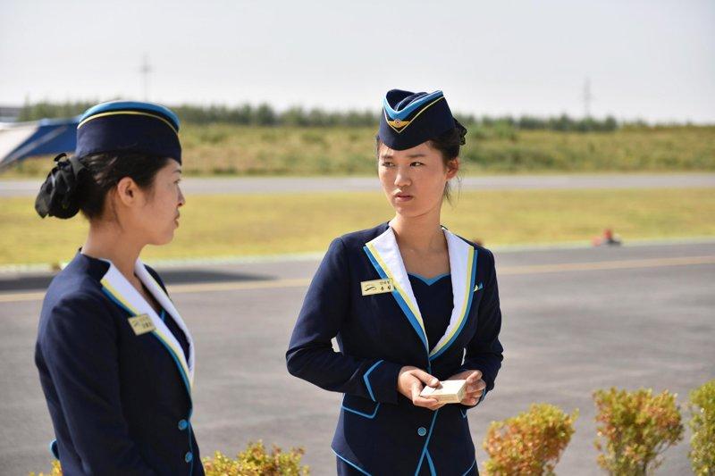 Две сотрудницы лётного клуба стоят около взлётной полосы Арам Пан, Пхеньян, видео, красота, редкие кадры, с высоты, фотограф