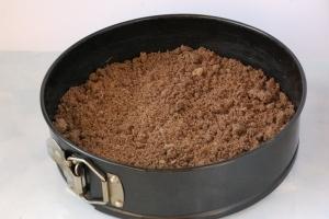 На дно формы (диаметр 23 см) выложить пергаментную бумагу и высыпать половину шоколадной крошки. Разровнять.