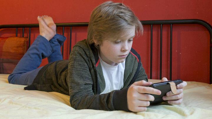 Ребёнок, смартфон, кровать: привычная картина. Источник фото Global Look Press.