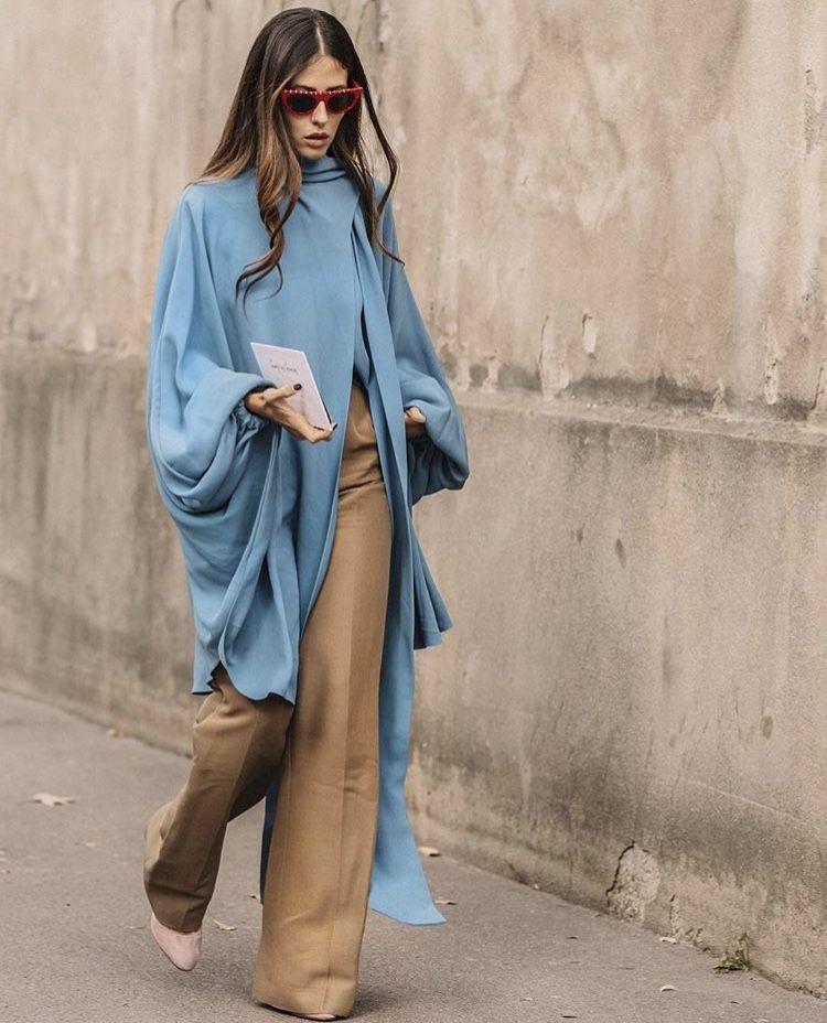 Девушк в голубой накидке и бежевых брюках клеш