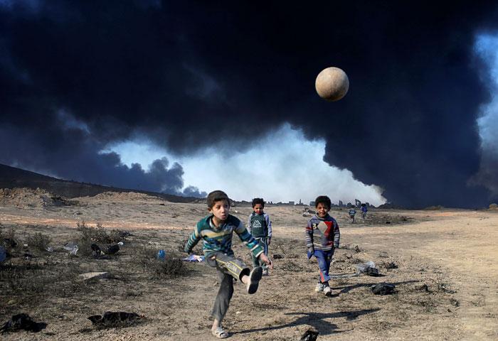 Дети играют в футбол на фоне подожженных боевиками ИГ нефтяных месторождений вблизи города Мосул