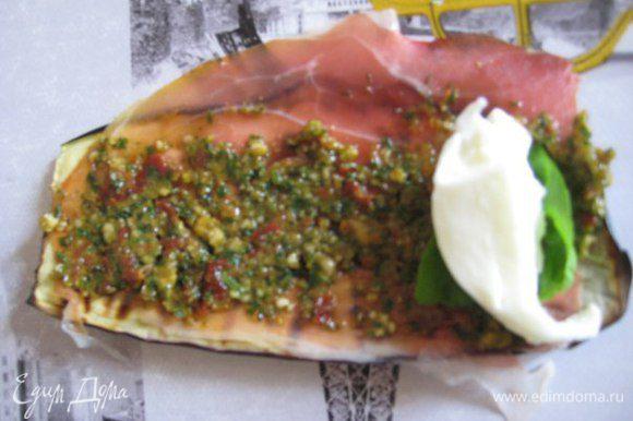 Моцареллу нарезать кусочками. На пластинку баклажанов выложить по ломтику прошутто (сыровяленой ветчины), нанести пасту. Положить кусочек моцареллы, листик базилика, свернуть в рулетик.