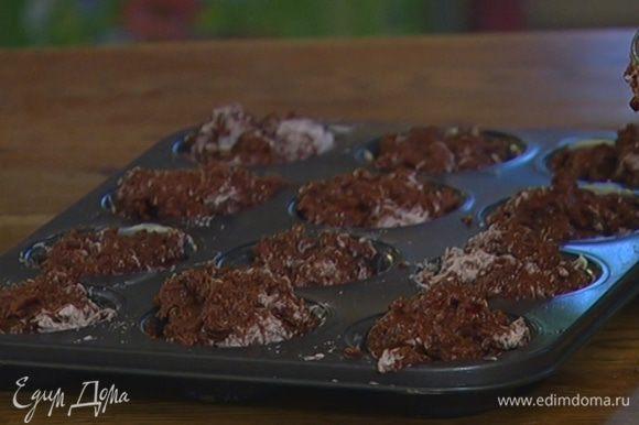 Формы для маффинов смазать оставшимся сливочным маслом и разложить тесто, заполняя формы не до самого верха.