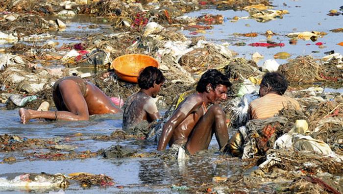Местные жители купаются в реке прямо посреди мусора.