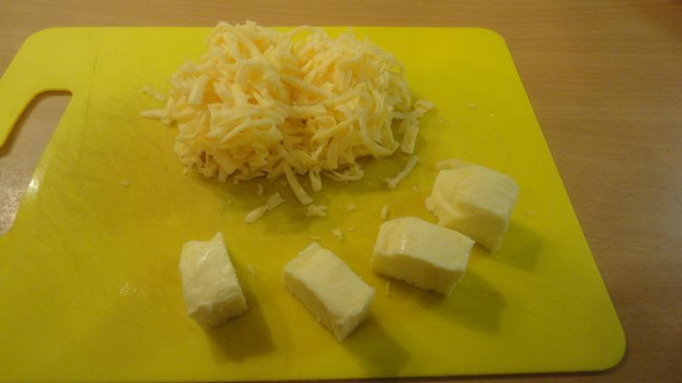 В каждый из горшочков нужно положить по небольшому кусочку сливочного масла и сверху присыпать его тертым сыром