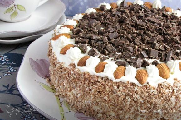 Взбить сливки с сахарной пудрой и выложить на третий корж. Также промазать сливками бока торта. Измельчить вафли в крошку и обсыпать бока торта. Украсить миндалем и шоколадом или цукатами по своему вкусу. Торт готов!