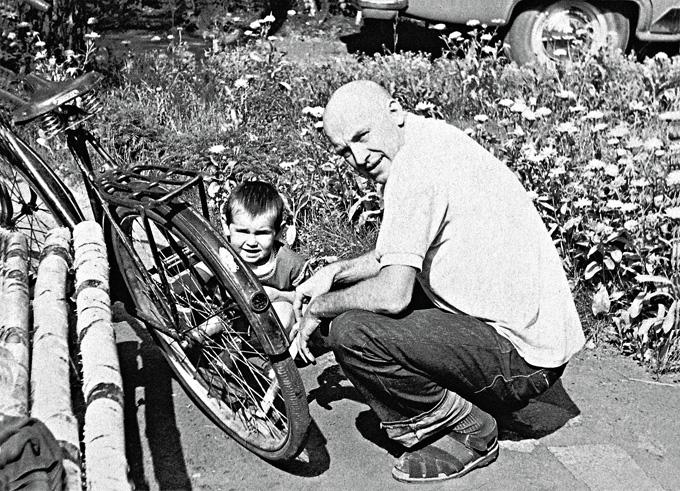 1084 Смоктуновский с дочерью Машей накачивают на даче шину велосипеда, 1968 г. В то время Иннокентий Михайлович готовился к съемкам в фильме «Чайковский» и, чтобы парик лучше сидел, побрился наголо.jpg