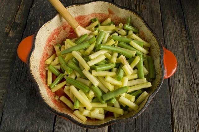 Фасоль выкладываем в кипящую томатную пасту. Добавляем растительное масло, соль и сахар
