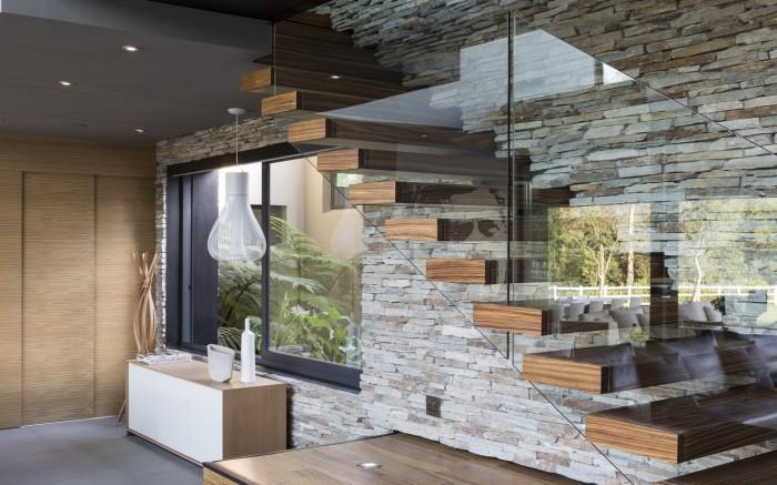 Лаконичный дизайн лестницы, сделанной из дерева, стекла и камня, гармонично вписался в интерьер дома.
