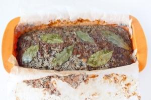 Ставим форму в предварительно разогретую до 180 °C духовку и выпекаем 1 час. Когда паштет будет готов, даём ему полностью остыть, затем вынимаем из формы и освобождаем от бумаги. Паштет можно также поставить на некоторое время под гнёт, чтобы в дальнейшем удобнее было нарезать.