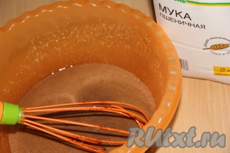Затем соединить яичную и шоколадную смеси. Перемешать венчиком. Добавить небольшими порциями просеянную муку.