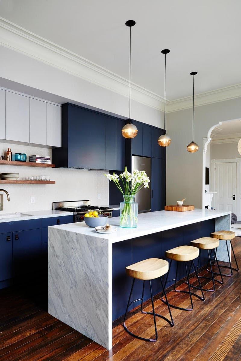 Глубокий синий часто используется в кухонных интерьерах в сочетании с белым мрамором. Этот тандем уже давно зарекомендовал себя с лучшей стороны.