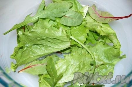 На дно салатницы разместить слой листовой зелени.