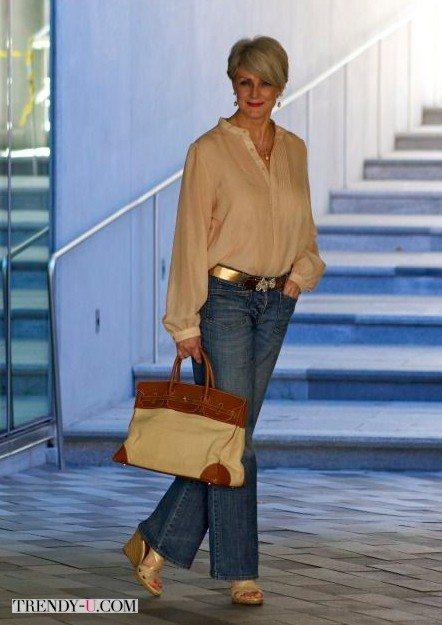 Бежевая блузка в сочетании с расклешенными джинсами на женщине среднего возраста