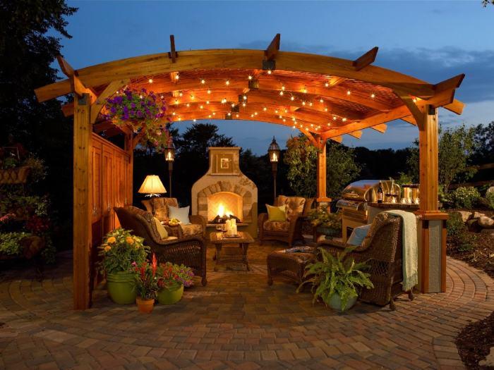 Беседка с легким романтическим освещением, барбекю-комплексом и камином.