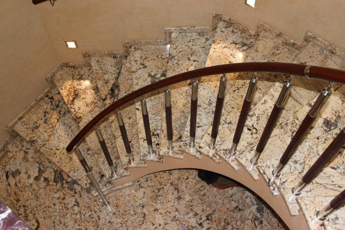 Эффектная спиральная лестница с металлическими перилами, выполненная из декоративного мрамора.