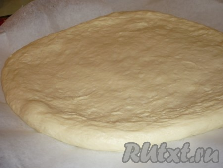 Большую часть теста на бумаге для выпечки раскатываем в круг - это и будет основа пирога.
