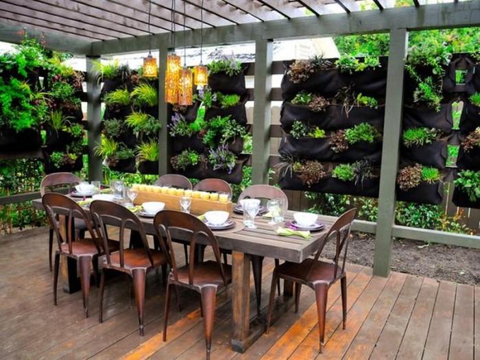 Открытая беседка с обеденным столом, окруженная зеленью.