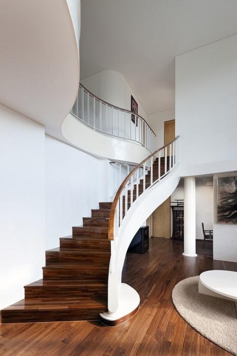 Необычная изогнутая лестница из тёмной породы древесины с односторонними перилами прекрасно впишется в интерьер дачи.