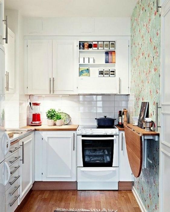Скромная кухня с классическими шкафчиками и складным столиком.