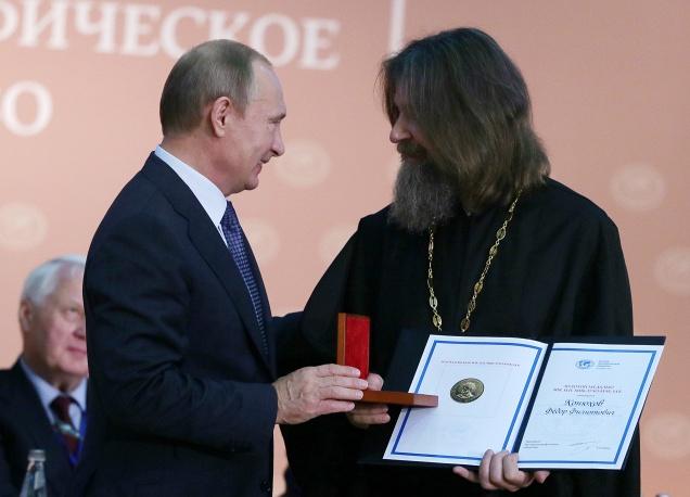 Президент Владимир Путин вручает золотую медаль имени Миклухо-Маклая Русского географического общества путешественнику священнику Федору Конюхову