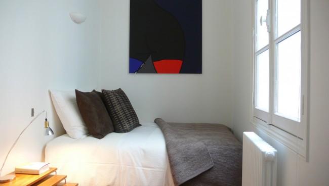 На фоне светлой отделки спальной комнаты любое проявление цвета будет выглядеть выигрышно, а уж геометрические рисунки или абстрактные картины точно станут центром фокусировки внимания