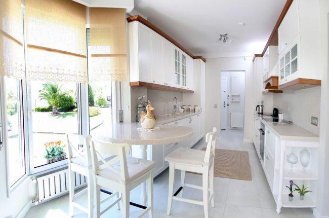 Отсутствие естественного освещения на кухне-коридоре может стать проблемой: установите панорамные окна в обеденной зоне и выберите светлый кухонный гарнитур, чтобы решить проблему