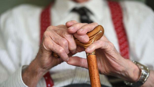 Руки пожилого мужчины на трости