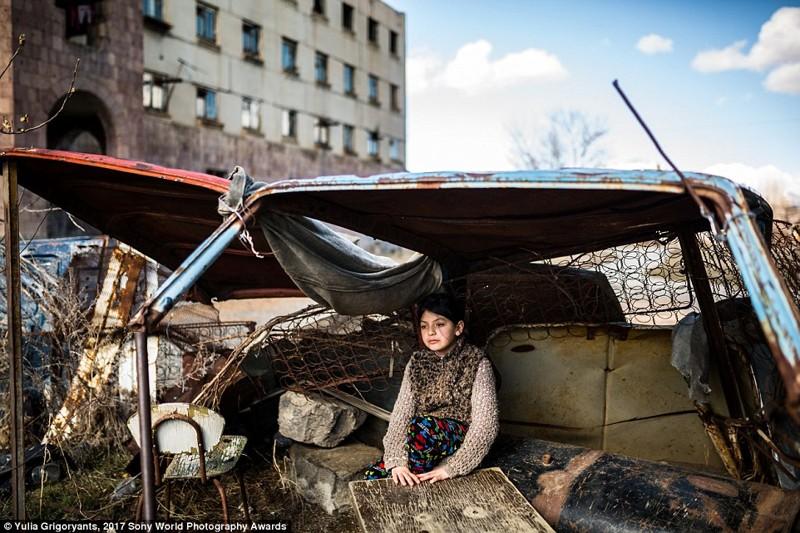 9-летняя Сюзанна сидит в ржавой машине напротив заброшенного здания, где она живет, Гюмри, Армения в мире, дети, жизнь