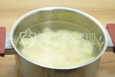 В кастрюлю выложить картофель и залить водой, поставить варить до готовности.