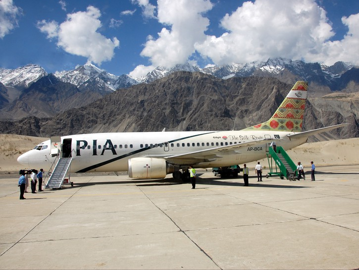 Pakistan International Airlines flight on tarmac with passengers boarding, mountains in the backgrou