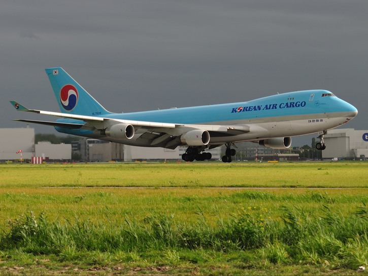 Korean Air cargo plane on runway, dark clouds in background