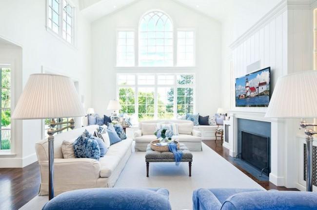 Голубые элементы в интерьере гостиной выглядят намного теплее в сочетании с мягкой мебелью и торшером сливочного цвета