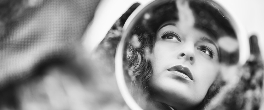 Face reflection on mirror of beautiful pensive woman