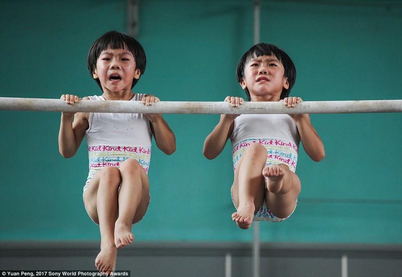 Девочки-близнецы на тренировке по гимнастике в китайской спортивной школе в Цзинине, провинция Шаньдун в мире, дети, жизнь