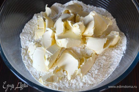 В большую миску просеять муку и добавить кусочки сливочного маргарина.