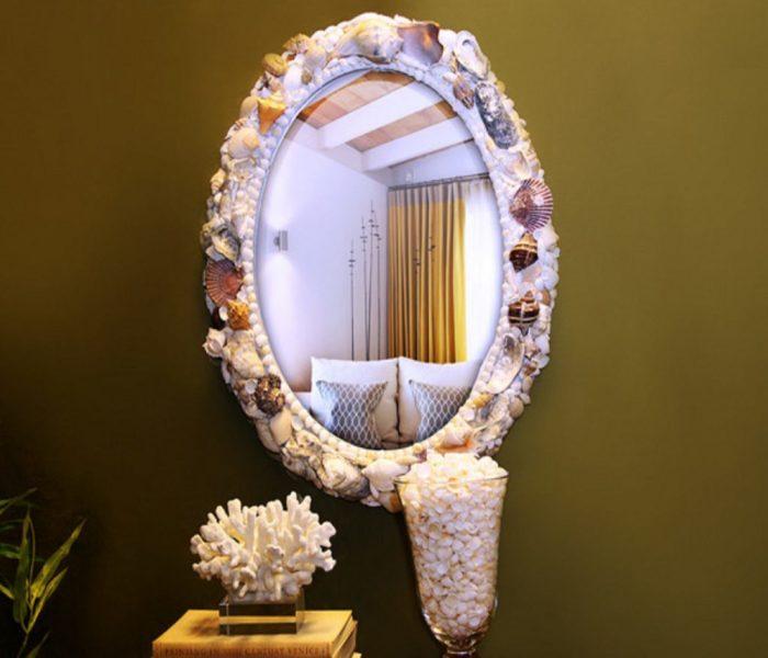Зеркало, декорированное ракушками и мелкой галькой в морском стиле.