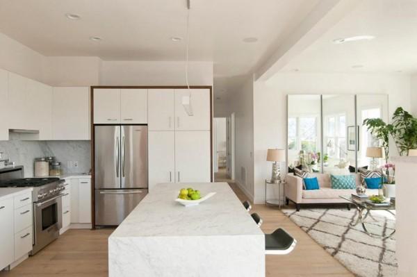 Современный интерьер кухни-гостиной в частном доме в белом цвете