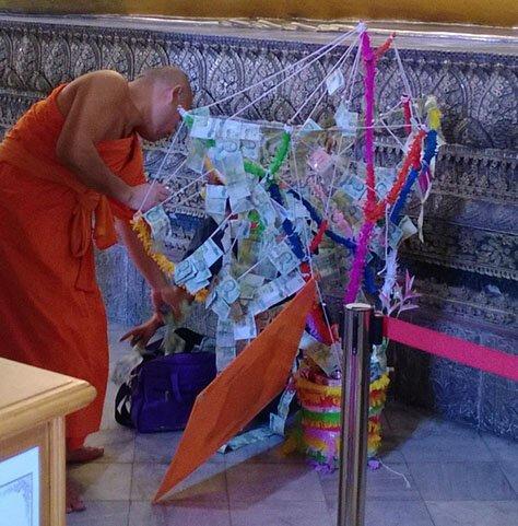 Тайские монахи достают из огромной сумки купюры, чтобы украсить ими «денежное дерево» страны, факты, это интересно