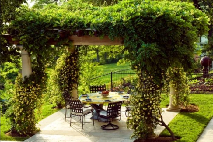 Беседка, украшенная живой изгородью из растений и цветов является прекрасным местом для отдыха в знойный день. | Фото: altanka.com.ua.