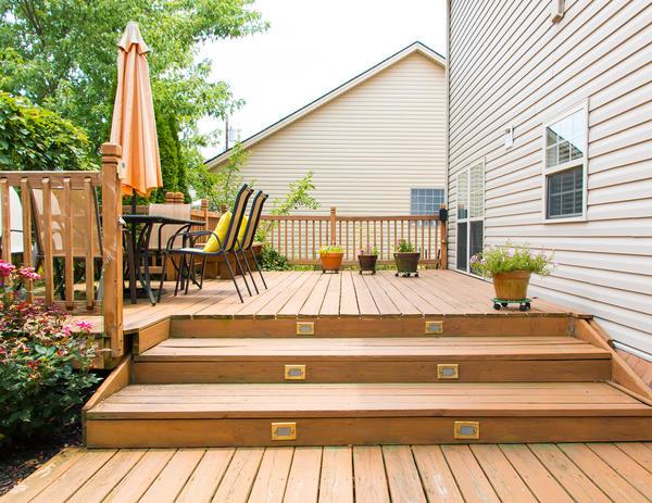 Заменой мощения в зоне патио может выступать деревянный садовый помост