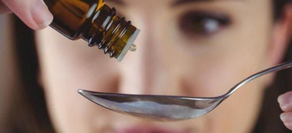 Женщина капает лекарство в ложку