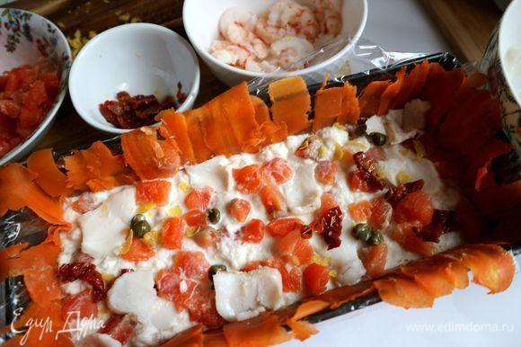 Повторить слой: красная рыба, лимонная цедра, каперсы, вяленые в масле помидоры, кусочки трески.