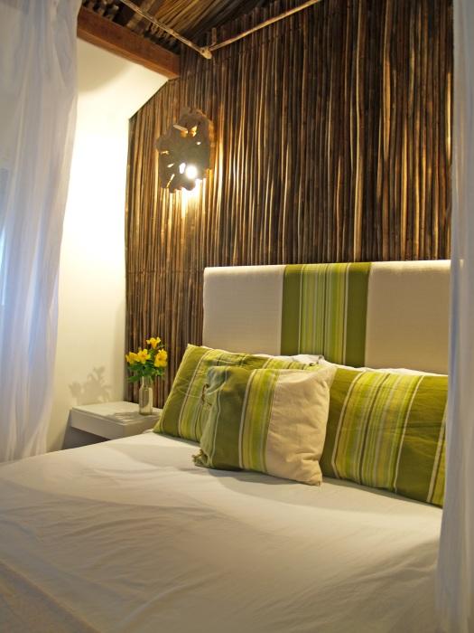 Стена из бамбука - частичка природы в интерьере спальной комнаты.
