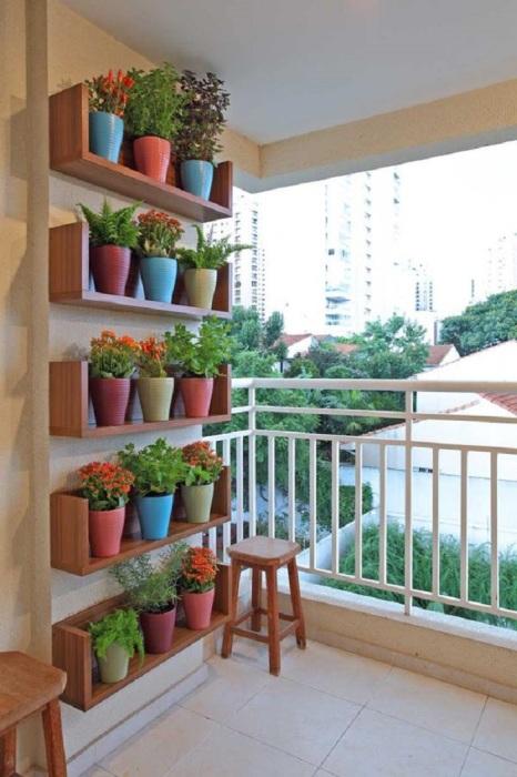 Не загромождайте стены шкафами на балконе, задекорируйте стену из замечательной композиции цветков в горшках.