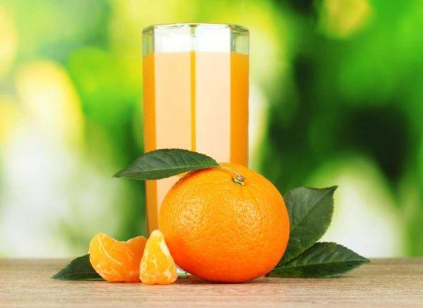 Стакан мандаринового сока, мандарин с листиками, дольки