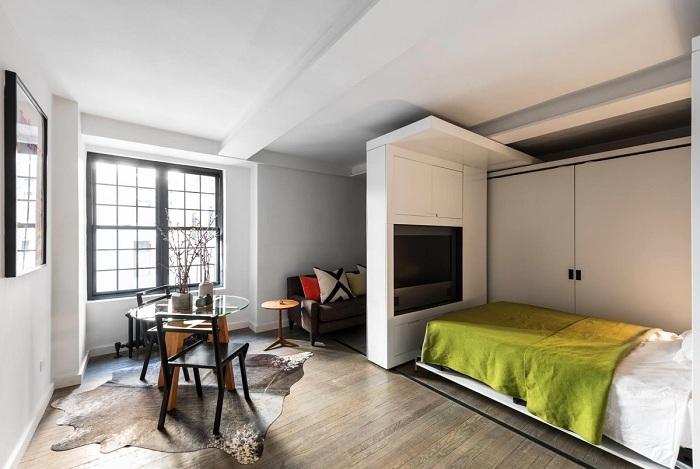 Передвижная стена по-разному зонирует пространство в квартире-студии.